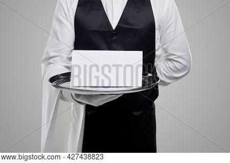 Crop Anonymous Waiter In Elegant Restaurant Uniform Carrying Tray With White Blank Paper Against Gra