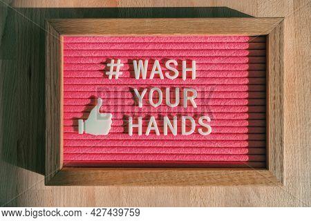 Wash your hands hashtag message on felt billboard board at business store good hand hygiene for coronavirus prevention. Felt sign for social media against COVID-19.