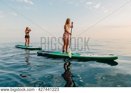 June 25, 2021. Anapa, Russia. Sporty Girls Float On Stand Up Paddle Board At Quiet Sea. Women On Red