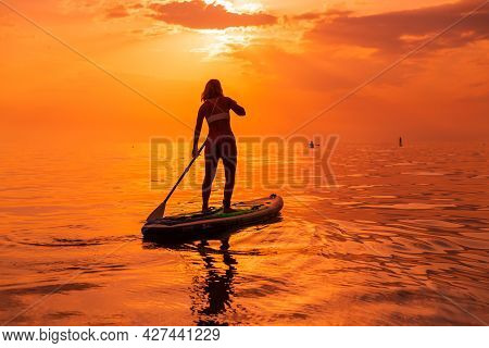 June 25, 2021. Anapa, Russia. Sporty Woman Paddle On Stand Up Paddle Board At Quiet Sea With Sunset