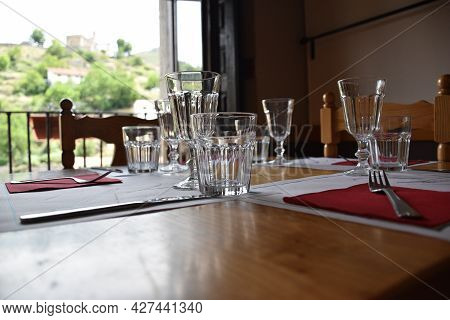 Crystal Glass On Assembled Table Ready To Eat. Defocused Background With Tableware And Window With M