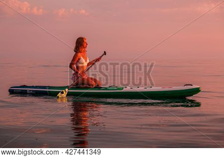 June 25, 2021. Anapa, Russia. Sporty Woman Relax On Stand Up Paddle Board At Quiet Sea With Sunset O