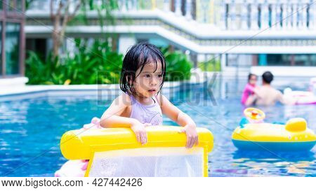 Asian Child In The Pool. Kid Holding Yellow Rubber Raft. Girl Wearing Purple Swimming Suit. Children
