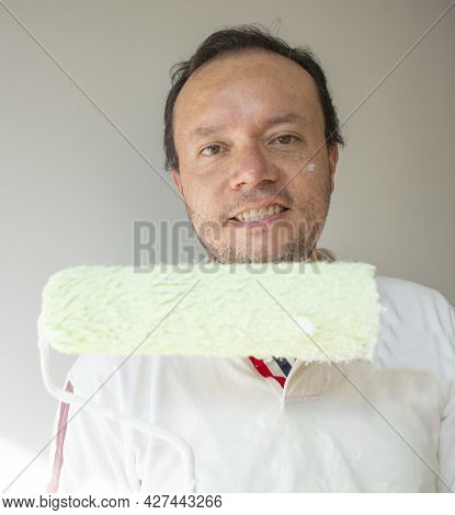 One Male House Painter Worker Painting And Priming Wall With Painting Roller.