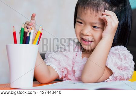 Happy Asian Child Girl Sweet Smiling. Kid Choosing A Wooden Crayon. Learning At Home. Children Aged