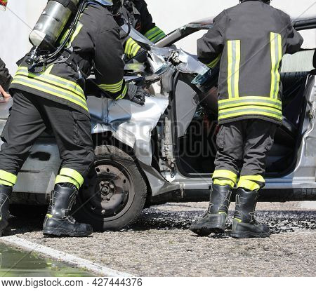 Firefighters With Apparatus Breathing During The Rescue After The Crash And The Damaged Car