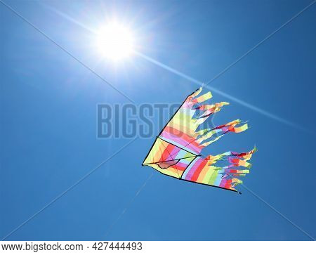 Sun And The Kite With Bright Colors That Flies High In The Sky Symbol Of Freedom And Carefree