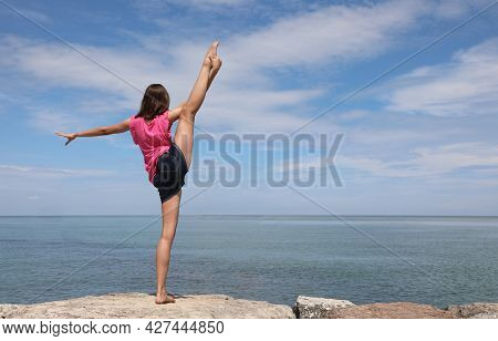 Caucasian Girl Performing Rhythmic Gymnastics Exercises With The Leg Up And The Foot Over The Head B