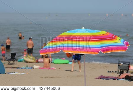 Colorful Parasol Umbrella On The Beach With Swimmers Having Fun During The Summer Holidays On The Sh