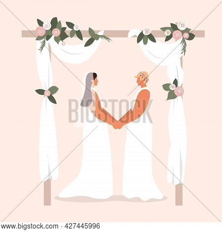 Happy Lesbian Couple. Lgbtq Wedding. Two Lesbian Brides Hold Hands Under A Beautiful Arch Decorated