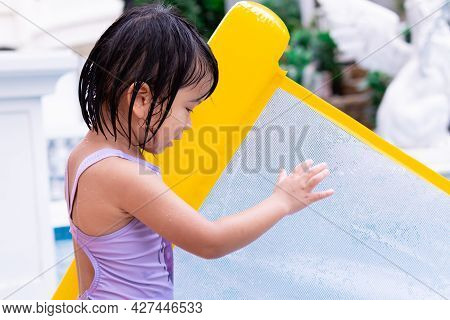 Side View Of Pretty Asian Child Holding Yellow Rubber Raft. Kid Playing Water In The Pool. Summer Da