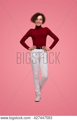 Full Body Of Smiling Confident Female Teenager With Curly Hair In Glasses Wearing Skinny Red Turtlen