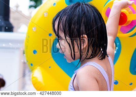 Adorable Asian Girl, Side View. Head Shot Of Child Playing Water Pool In The Summer. Kid Holding Yel