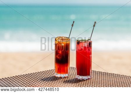 Fresh Cold Orange And Raspberry Cocktails On Table On Beach With Sunny Sea On Background. Fruit Mock