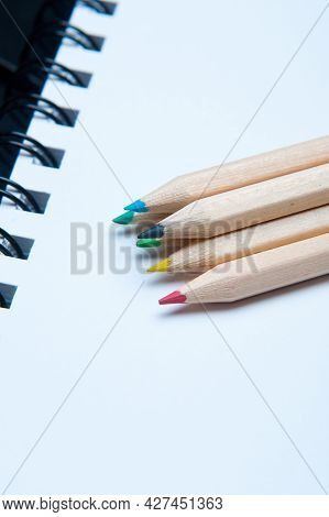 Close-up Of A Pile Of Colorful Wooden Pencils Arranged Over A White Notepad. Six Elements.school Con