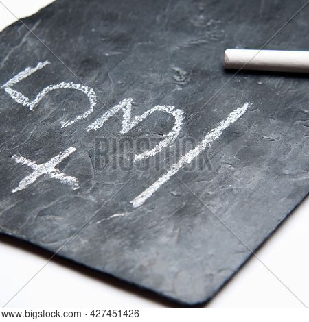 Simple Maths On A Blackboard With Chalk. White Background.