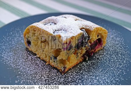 Closeup Of A Slice Of Mouthwatering Blueberry Cake Sprinkled With Icing Sugar
