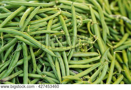 Pile Green String Beans Displayed On Food Market. Abstract Healthy Nutrition Background - Shallow De