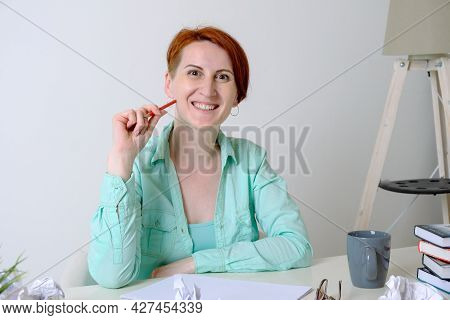 Young Woman In Informal Clothes Sits At A Desk In Front Of A Blank Sheet Of Paper. The Woman Smiles
