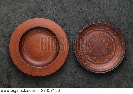 Two Rustic Plates On Gray Background. Empty Brown Clay Plate On Black Stone Table. Top View With Cop
