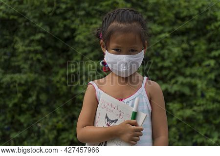 Little Asian Girl Wearing Face Mask With Green Back Pack Holding Stationery In Green Nature  Park Ba