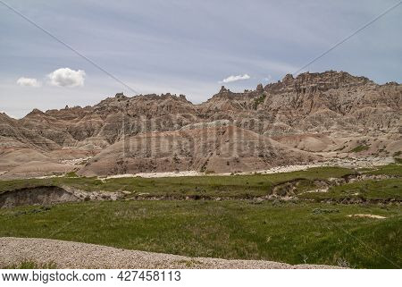 Badlands National Park, Sd, Usa - June 1, 2008: Mountain Range With Red Topped Geological Outcrop An