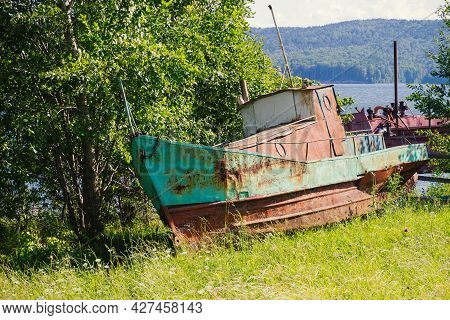 Rusty Metal Abandoned Boat Was Left On The River Shore