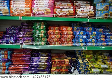 Supermarket Aisle Of Biscuits, Snacks, Cookies. Various Brand Biscuits Display On The Supermarket Ai