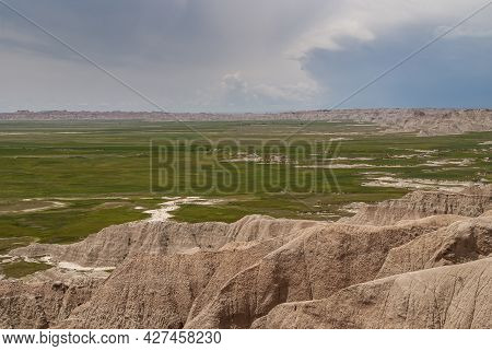 Badlands National Park, Sd, Usa - June 1, 2008: Looking From Top Of Beige Mountains Over Flat Green
