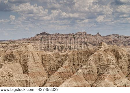 Badlands National Park, Sd, Usa - June 1, 2008: Wide Landscape Filled By Beige Mountains And Heavy B