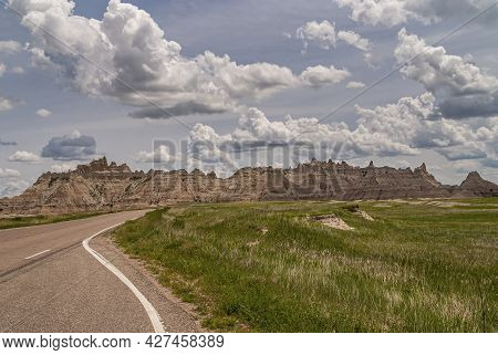 Badlands National Park, Sd, Usa - June 1, 2008: Road On Side Of Green Prairie In Front Of Brown Moun