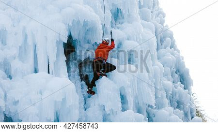 Man Climbing On A Frozen Steep Slope, Passing Between Large Bumps, Ridges, And Icicles