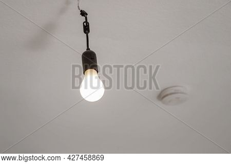 Naked Dusty Light Bulb Without Lampshade Hanging Switched On From The Ceiling In An Empty Apartment,
