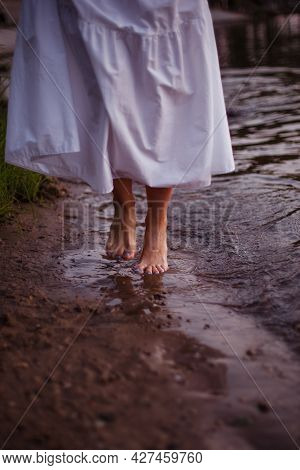 Womens Feet In The River. Close-up Front View Of The Feet Of A Woman In A Long Summer Sundress Walki