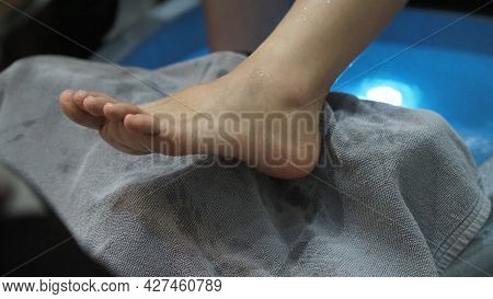 Foot Spa. Woman Bare Feet Massaging In Soap Water Machine At Spa Shop.