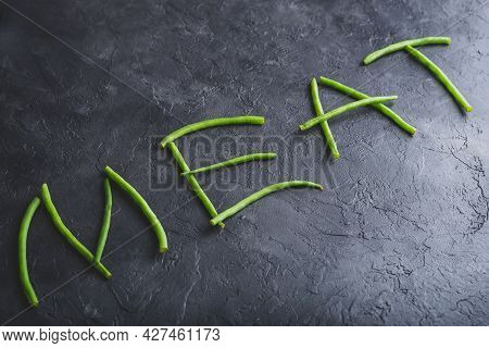 Word Meat Spelled Out In Fresh Pods Of Green Beans On Dark Concrete Background