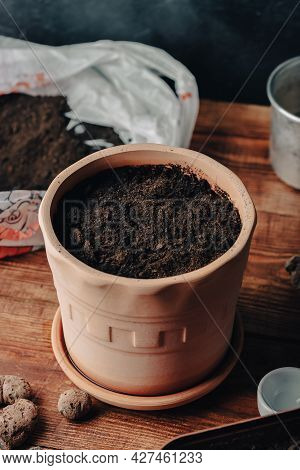 Clay Flower Pot Full Of Potting Soil And Sowed Seeds Of Thyme On Rustic Wooden Table