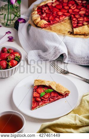 Slice Of Sweet Fresh Baked Strawberry Galette With Mint Leaves On White Plate