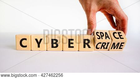 Cyber-space Vs Cybercrime Symbol. Businessman Turns Wooden Cubes, Changes Words Cybercrime To Cyber-