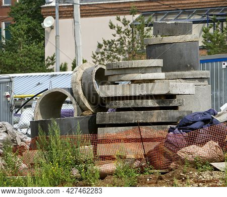 Building Materials Are Stored Behind A Mesh Fence. Concrete Rings And Blocks Are Stacked. The Filled