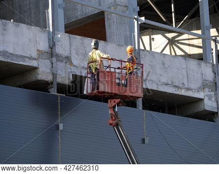 An Aerial Platform Lifts Workers To The Upper Floors Of A Building Under Construction. Background Wi