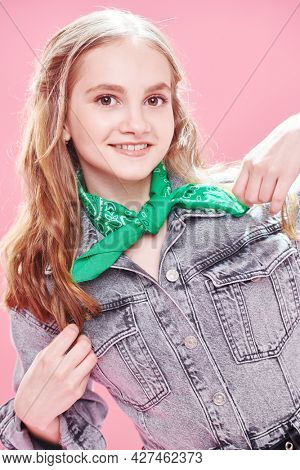 Portrait of a cute teenage girl in modern clothes smiling at camera on a pink background. Youth fashion.