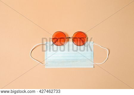 Red Round Sunglasses With Medical Mask On Brown Background. Banner Template With Goggles, Face Mask