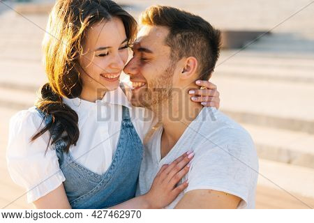 Close-up Portrait Of Cheerful Young Couple Resting In City Park Sitting Embracing On Bench In Summer