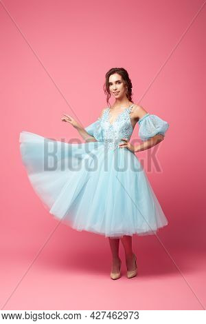 A Young Woman In A Ball Gown Stands At A Pink Background. A Beautiful Brunette In A Lush Blue Dress