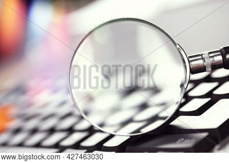 Magnifying Glass On The Keys Of A Black Computer Keyboard