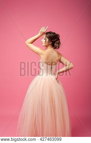 A Young Woman Stands With Her Back Against An Isolated Background. A Beautiful Woman Model In A Beig