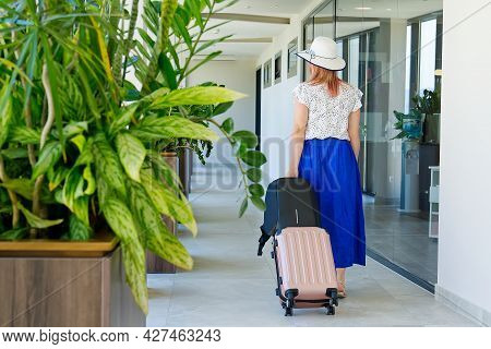Girl Tourist Checks Out Of The Hotel. Tourist With A Suitcase Walks Along The Corridor In The Hotel