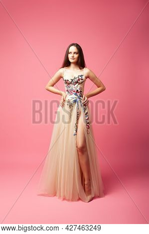 A Young Woman In An Evening Dress Stands On An Isolated Background. A Beautiful Woman In A Lush Ball