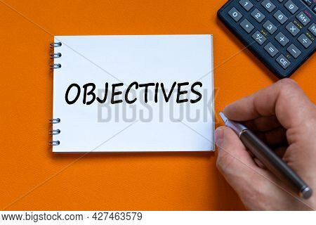 Objectives Symbol. Businessman Writing The Word Objectives On White Note. Black Calculator. Beautifu